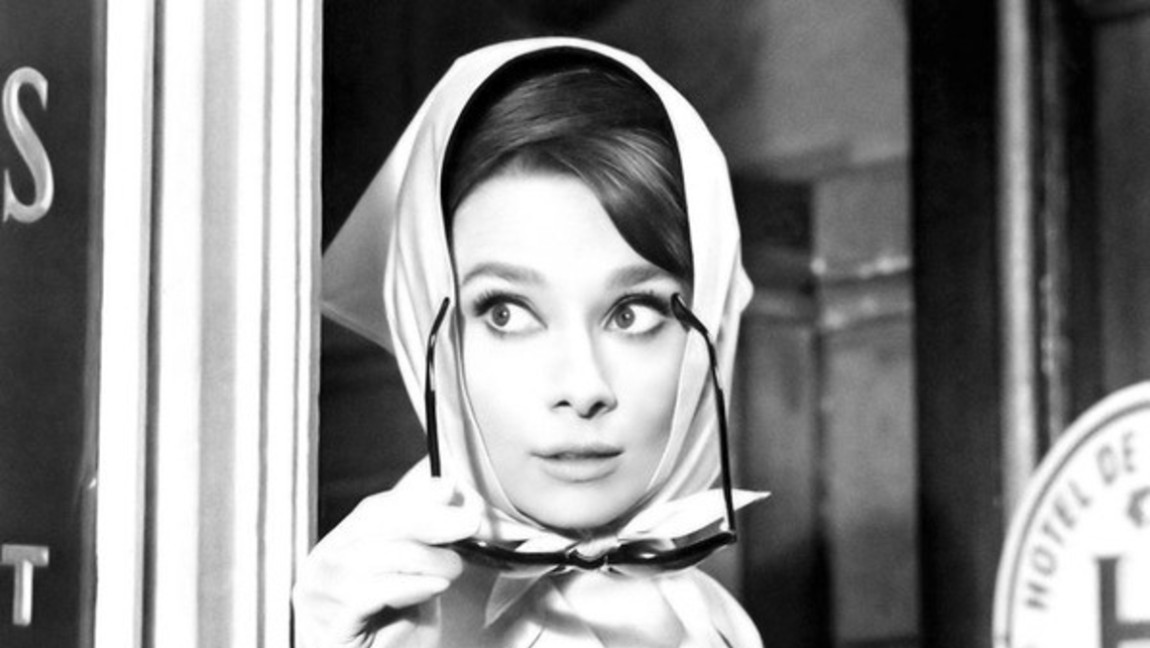 Audrey Hepburn wears a silk scarf around her head while holding sunglasses.