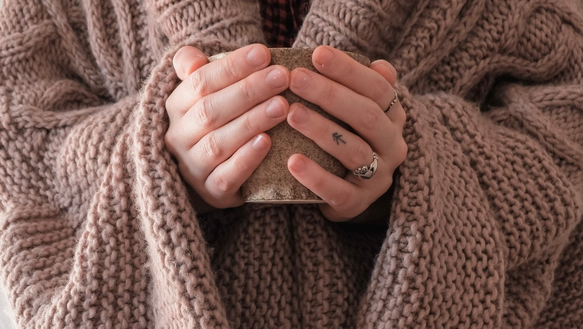 A sweater is worn by someone holding a mug. Via Unsplash