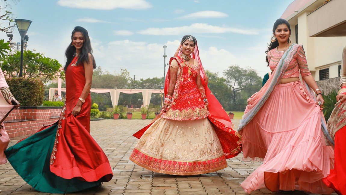 Women in traditional South Asian clothing pose. Via Unsplash.
