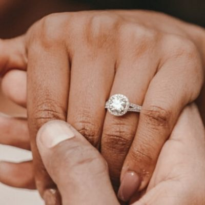 [Image Description: A womans hand with an engagement ring with a man holding it.] via Unsplash