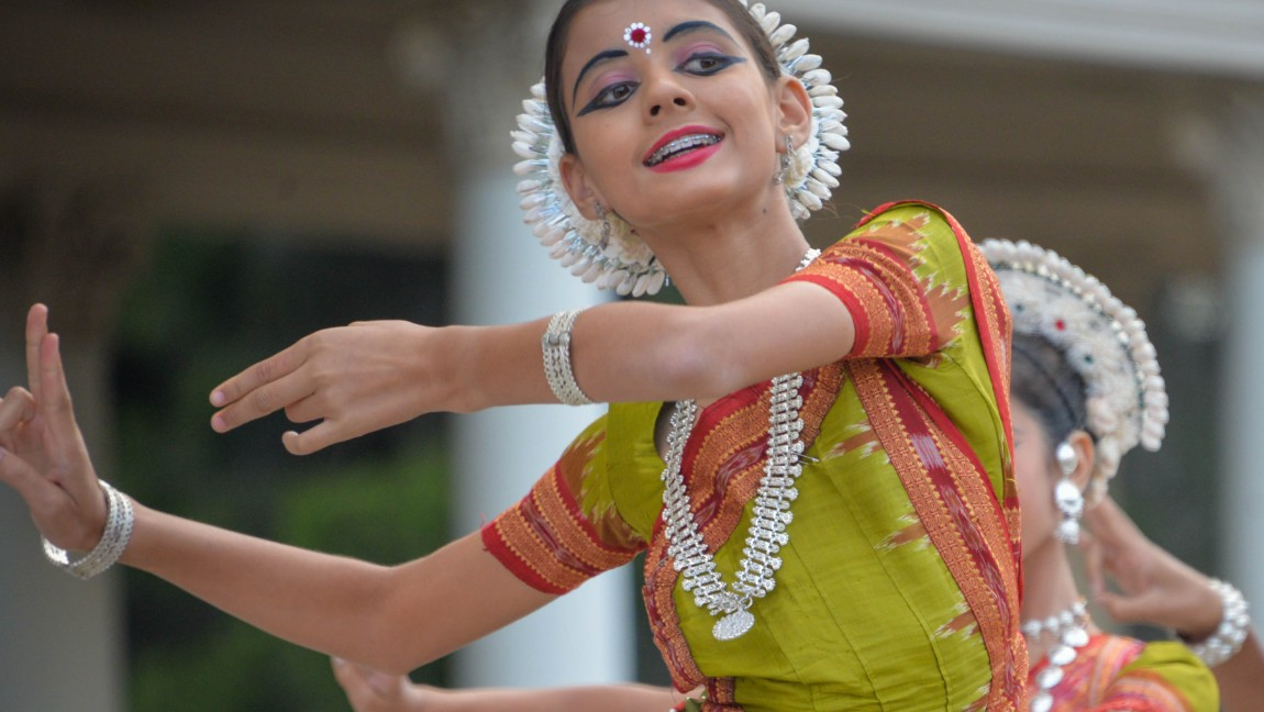 A dancer is dressed in traditional Indian clothes. Via Unsplash.
