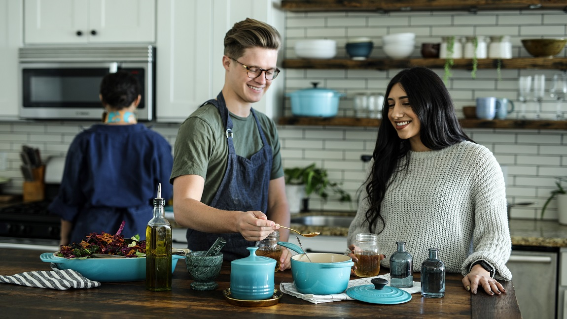 The image of a man and a woman cooking with another person behind them.