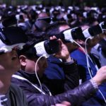[Image description: A crowd of people wearing virtual reality headsets sits in an auditorium.] via Maurizio Pesce