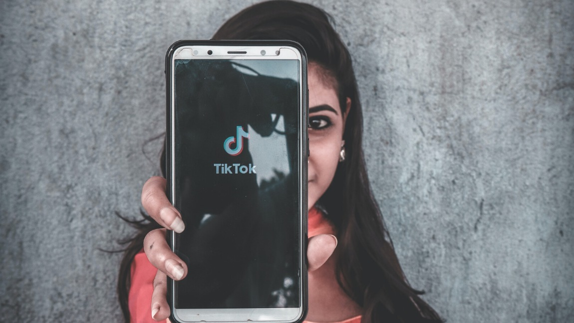 A woman holds a mobile phone with a TikTok logo facing the camera.