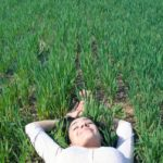 A woman lies on a field of grass with her eyes closed and hands above her head.