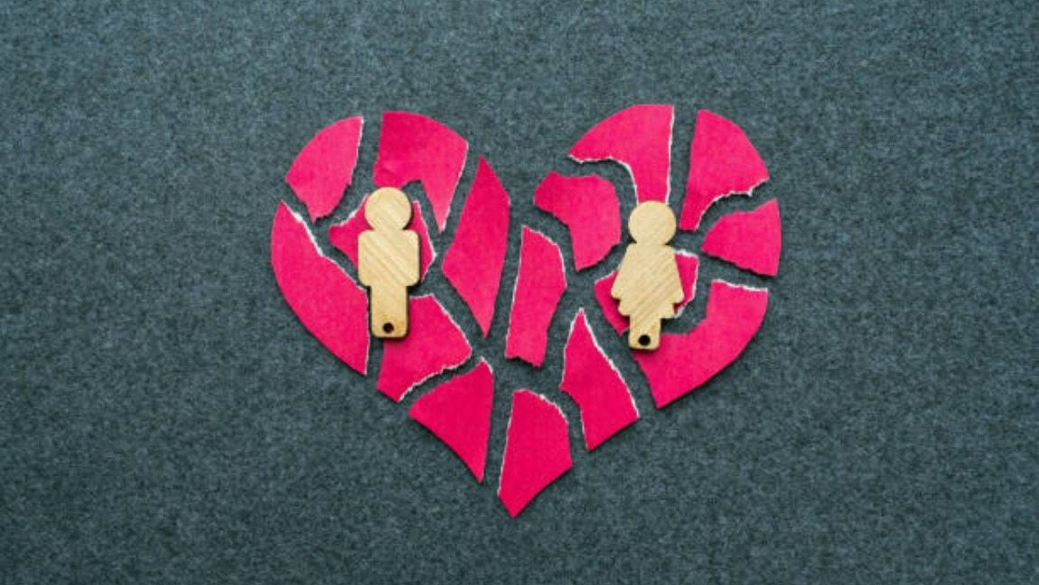 [Image Description: A broken heart with two wooden pieces shaped like a man and a woman on top of them.] via iStock