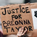 """A hand holds a cardboard sign that says """"Justice for Breonna Taylor."""" The tops of other heads in the crowd can be seen."""