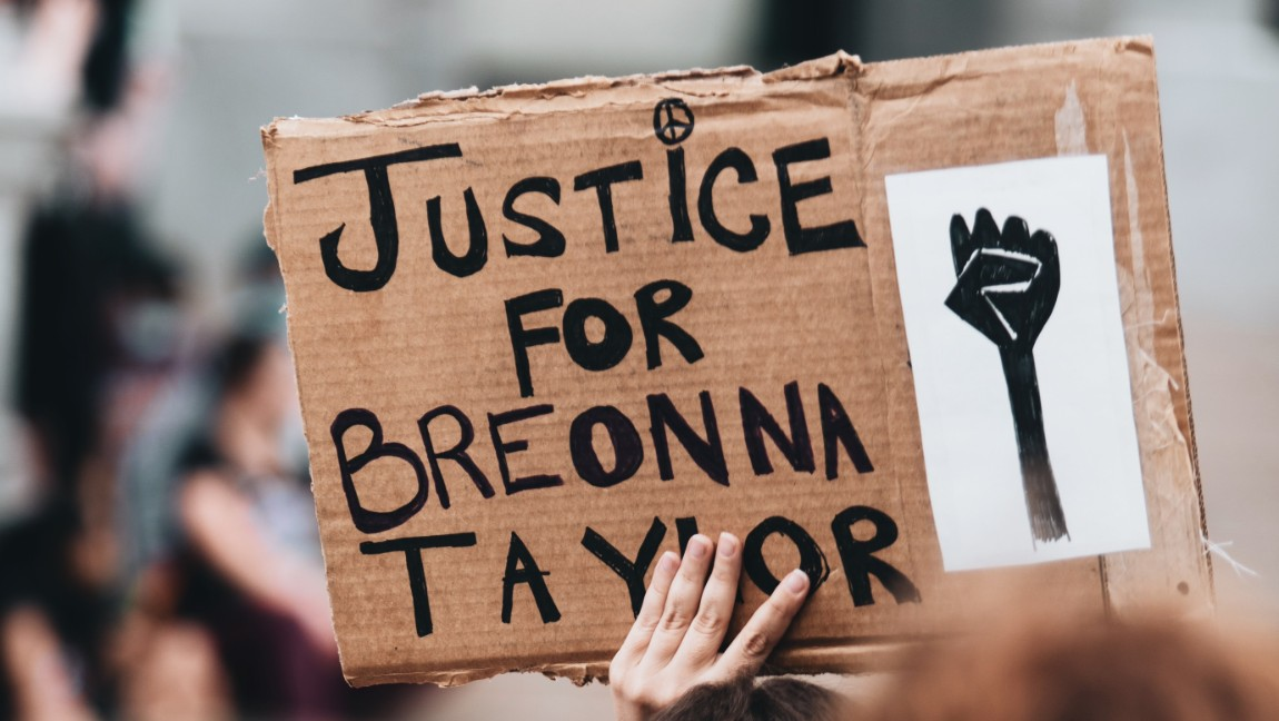 "A hand holds a cardboard sign that says ""Justice for Breonna Taylor."" The tops of other heads in the crowd can be seen."