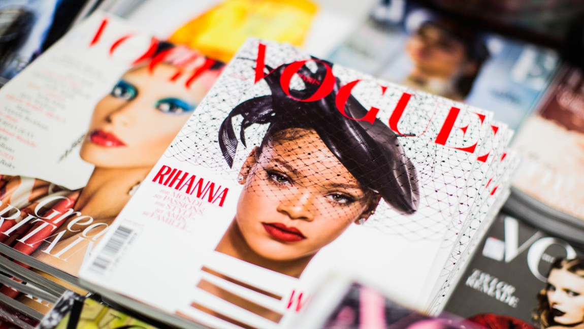 A display of different Vogue magazines spread out, the one at the center has Rihanna on the cover.