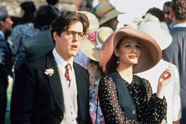 Charles (Hugh Grant) looking shocked and Fiona (Kristin Scott Thomas) looking amused standing outside during a wedding reception.