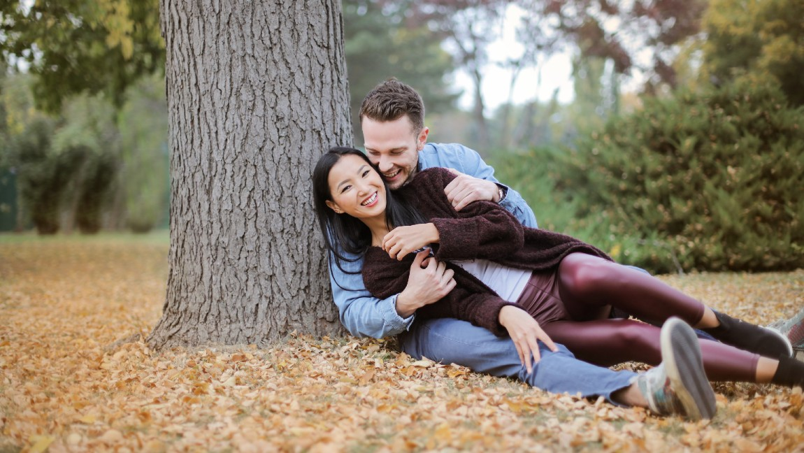 A man sitting at the base of a tree with his arms wrapped around a woman as they smile.