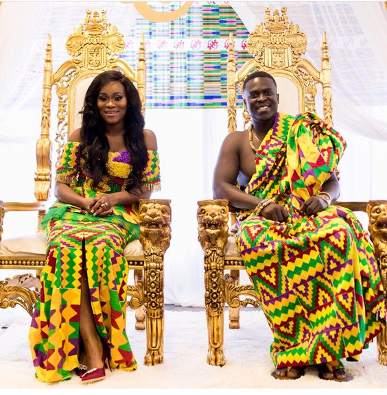 [Image Description: A newly-wed couple dressed in traditional Akan clothing sit side by side in golden thrones.] via Maxwell Jennings New York