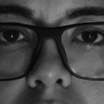 [Image description: A black and white image of the upper half of a woman's face with glasses.] Via Christelle Hayek on Unsplash