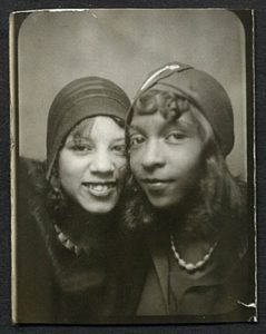 [Image Description: A vintage portrait of two women smiling at the camera, dressed in flapper style.] Via See Jane Sparkle