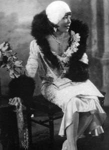 [Image Description: An African American flapper girl sits on a chair, wearing a fur hat, coat with feathery trim and extravagant dress.] Via See Jane Sparkle