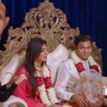 A bride and groom dressed in traditional Indian clothing are sitting down with guests next to them. Via Netflix.