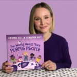 """Kristen Bell holding up her book, """"The World Needs More Purple People."""""""