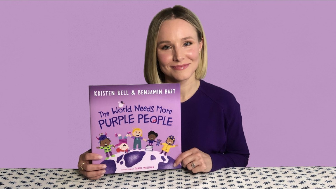 "Kristen Bell holding up her book, ""The World Needs More Purple People."""