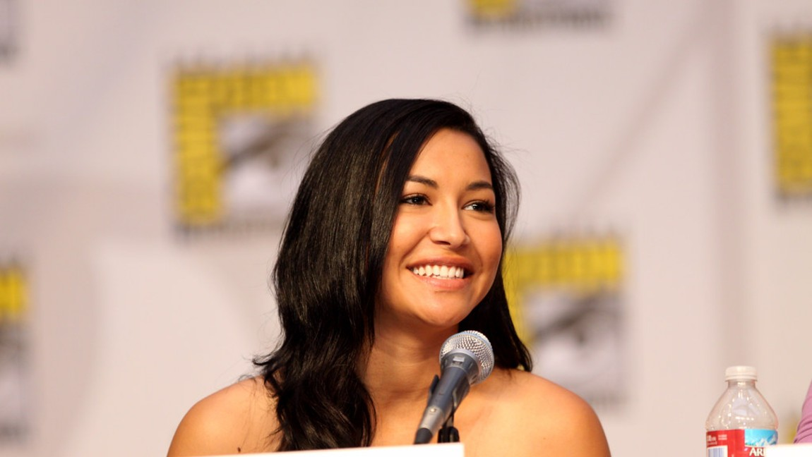 Actress Naya Rivera smiling with a microphone in front of her.