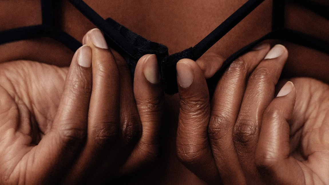 [Image Description: Woman unbuckles her bra from behind.] via Unsplash