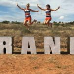 [Image Description: Two girls jump above a a sign that says 'Orania'] via ORANIA BEWEGING