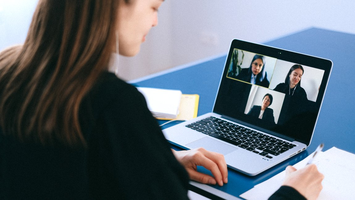A woman with headphones takes notes while on a video call with two other women.