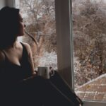 A girl sitting by a window and holding a mug in a dark room.