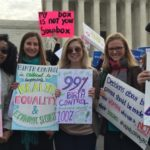 a group of people hold signs in favor of birth control rights in front of the Supreme Court.