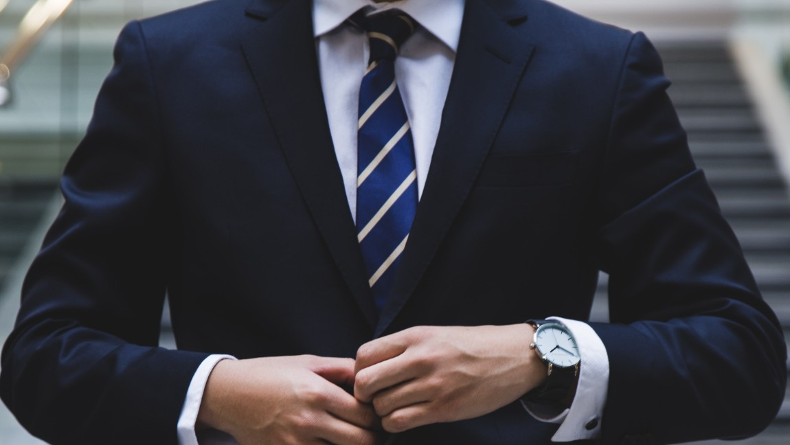 Two hands button a blazer. Via Unsplash