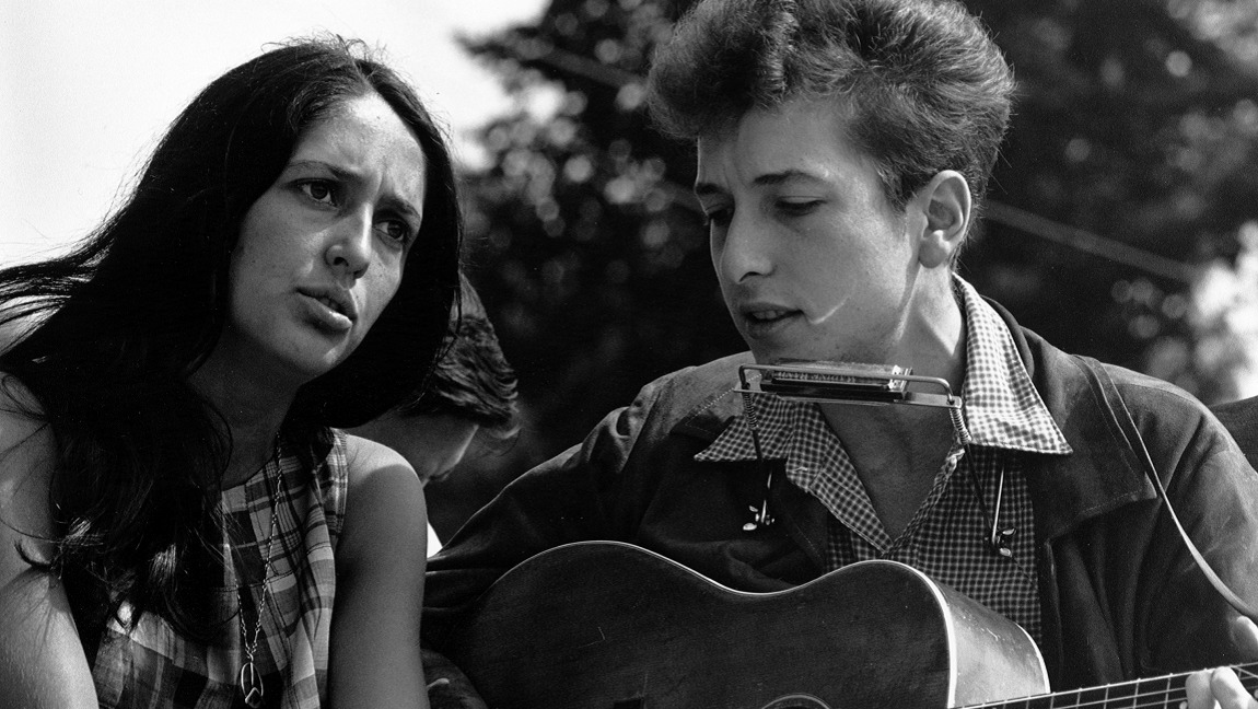 A black and white photo of a young Joan Baez and Bob Dylan with his guitar and harmonica performing protest music at the March on Washington, 1963.