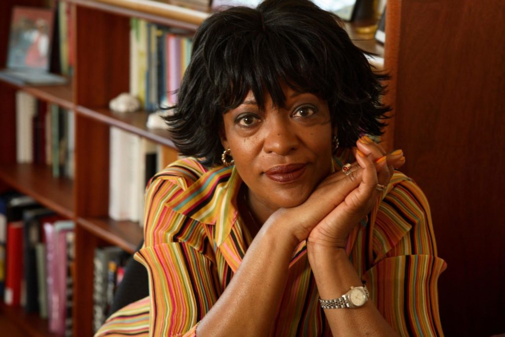Poet Rita Dove rests her hands on her face in front of a bookshelf.