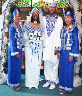 [Image Description: Blue traditional dress worn by husband and wife. Family members flank the happy couple clothed in blue traditional dress.] via Matix