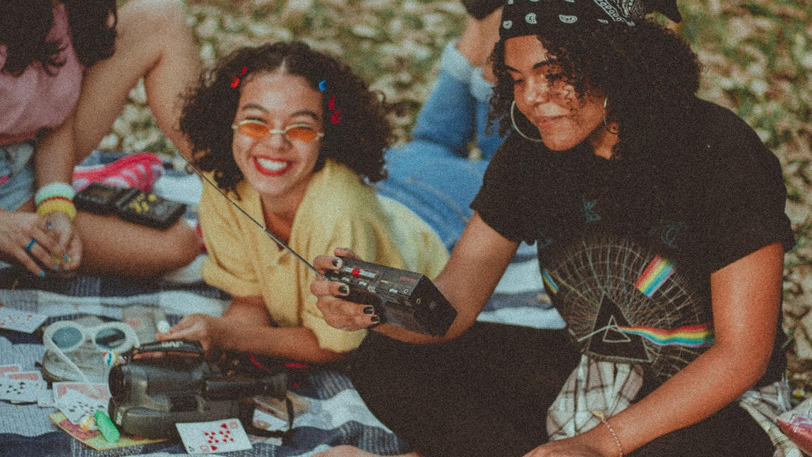 [Image Description: Two smiling women laying on a picnic blanket, one holding a black AM-FM radio.] Via Pexels.