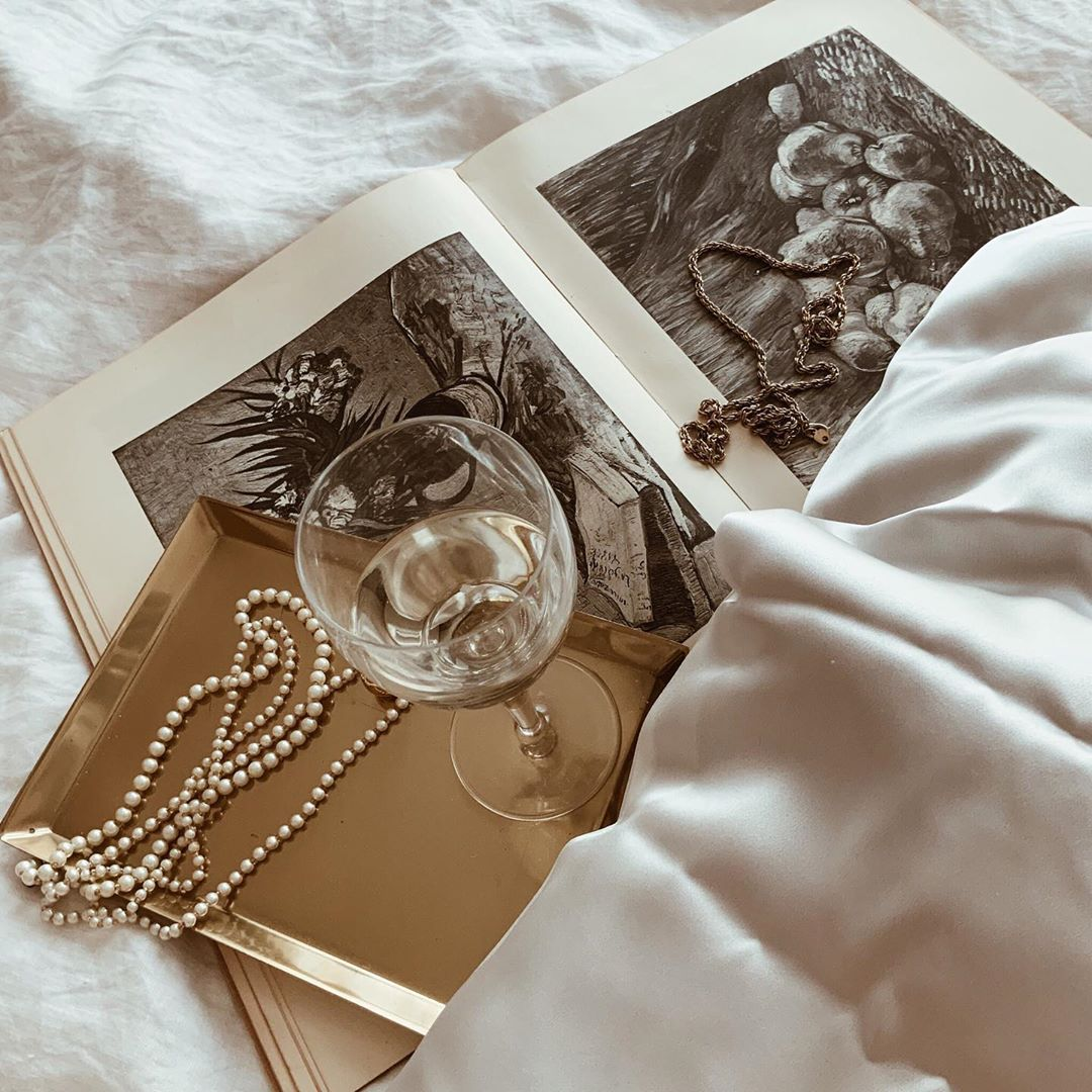 A book, wineglass, necklaces, and silk pillowcase are strewn on bedding.