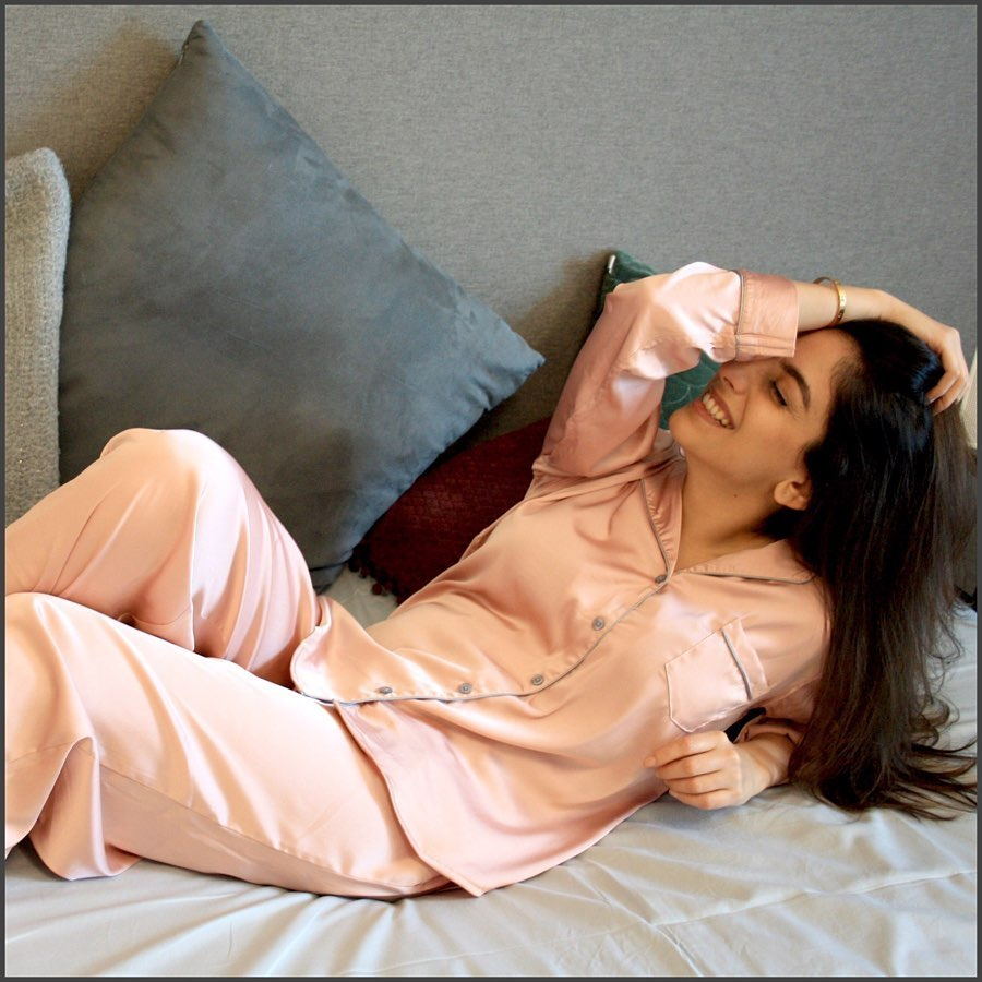 A woman running her hand through her hair leans back on a bed with pillows. She is wear a long-sleeved silk pajama top and bottoms.