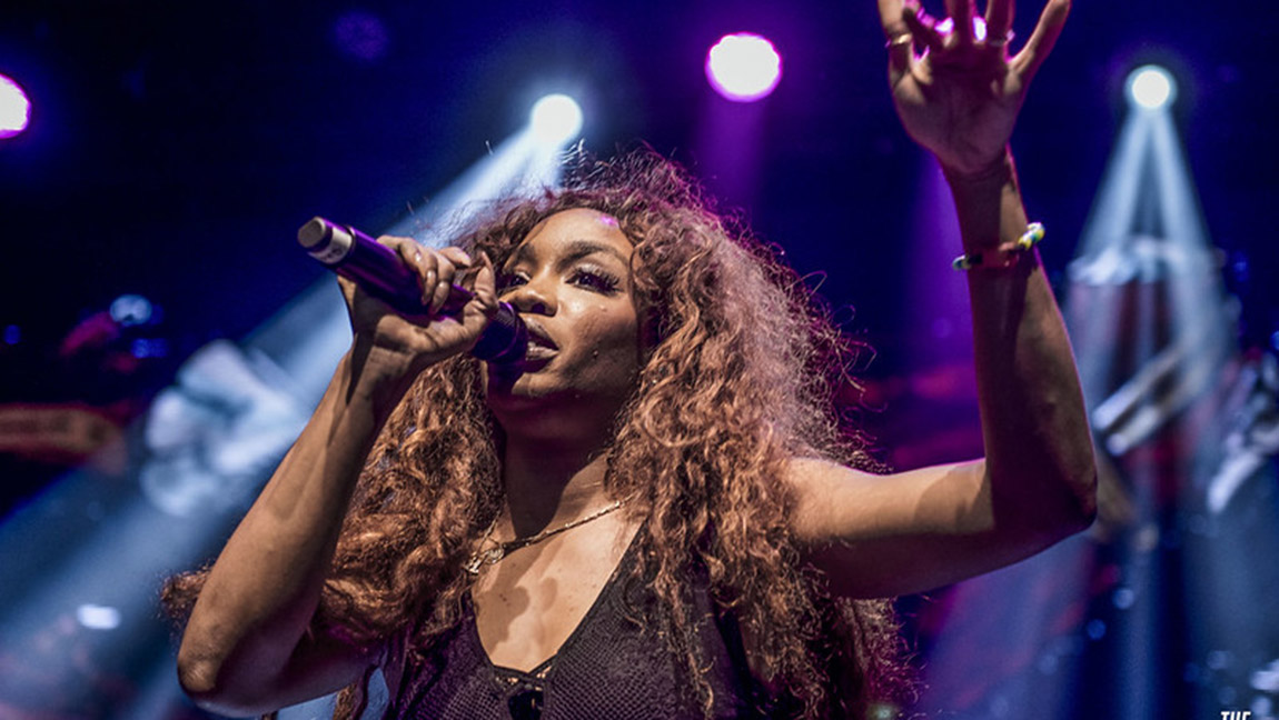 SZA holding a mic in one arm and singing amidst blue and purple stage lights