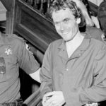 [Image Description: Ted Bundy being led away by police officers] via Ross Dolan, Coloradoan Library