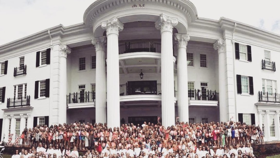 A group of sorority sisters gather for a photo in front of their house.