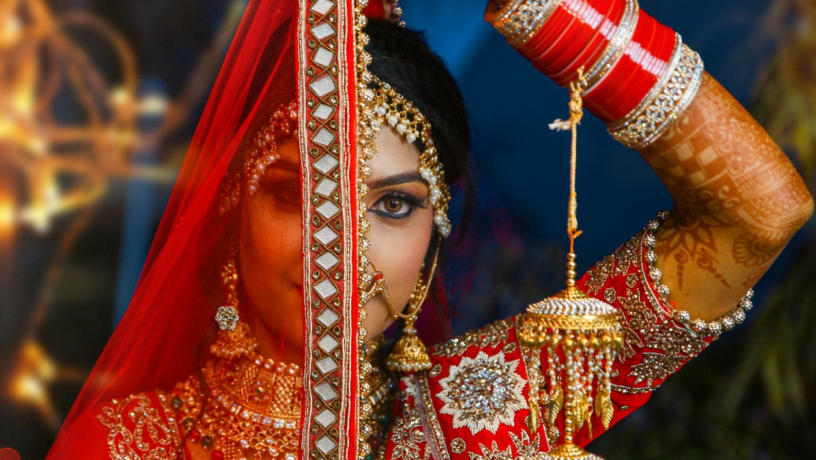A South Asian bride dressed in red and decked out in jewelry covering half her face with her dupatta.