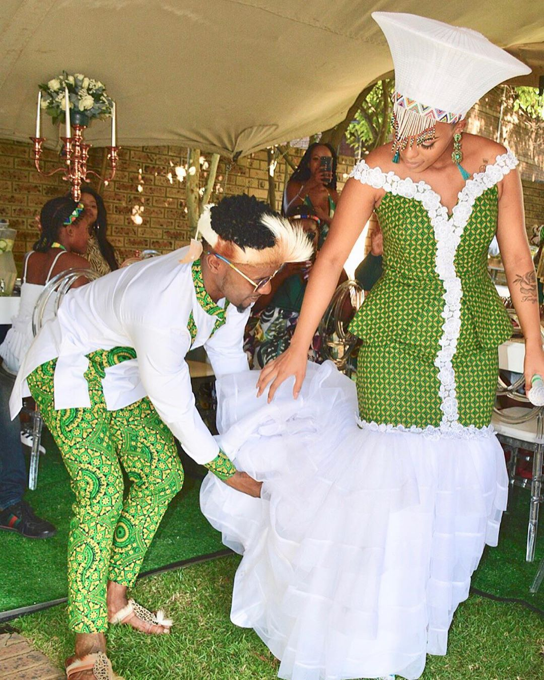 [Image Description: A newly-wed couple dressed in green traditional outfits for their ceremony. The groom fixes his wifes train.] via Abdul Khoza