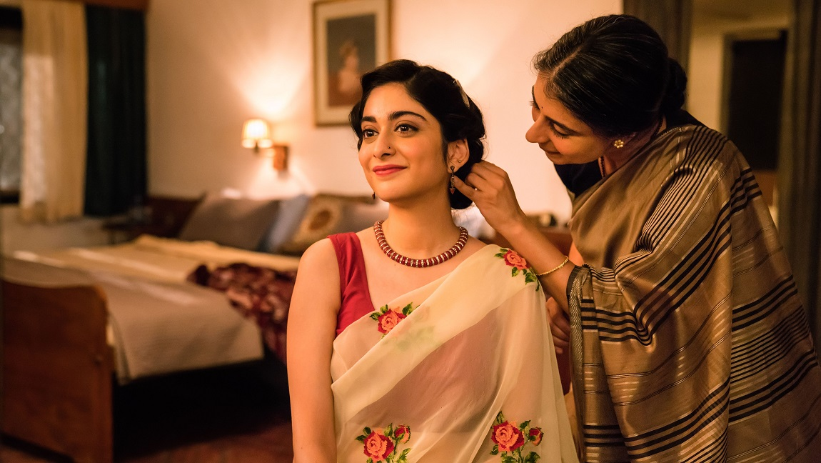 The image shows two women wearing sarees, while one woman is fixing the hair of the other.