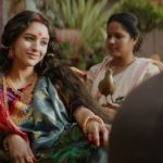 The image shows a still from the movie Bulbbul with two women wearing traditional Bengali wear.