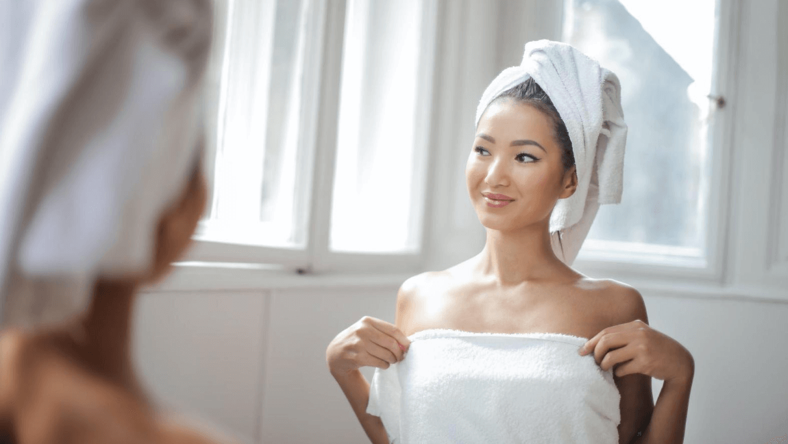 A woman in a white towel with a white towel on her head is smiling into the mirror.