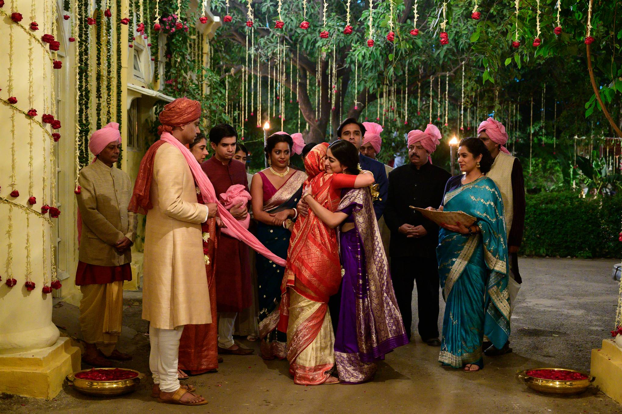 The image shows a scene from A Suitable Boy where a lot of people are hugging to bid farewell to a bride in her wedding.