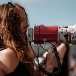 [Image Description: A young activist is addressing a protest with a loudspeaker] Via Unsplash