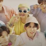 [Image Description: BTS looking up at the camera, while wearing colourful funky clothes, and making peace signs] via Pitchfork.com