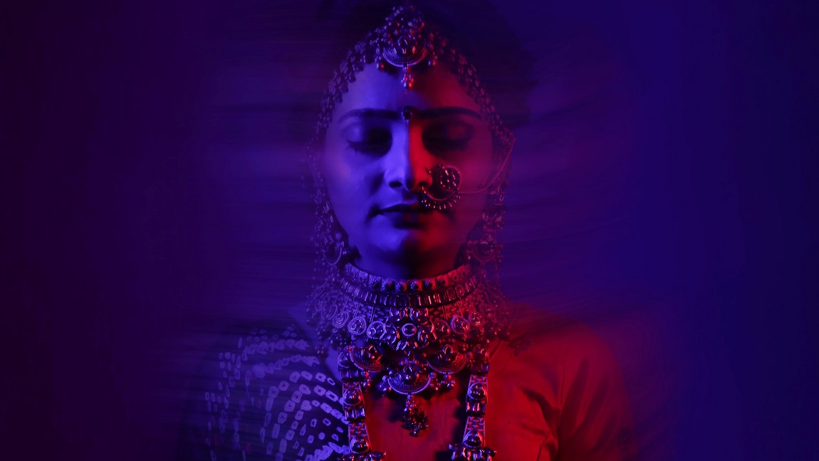 The blue and red image shows a woman ornately dressed in Indian attire.