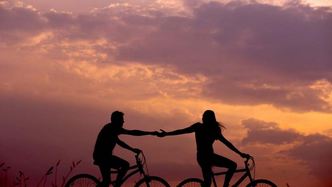 [Image Description: A man and a woman ride a bicycle] via Unsplash