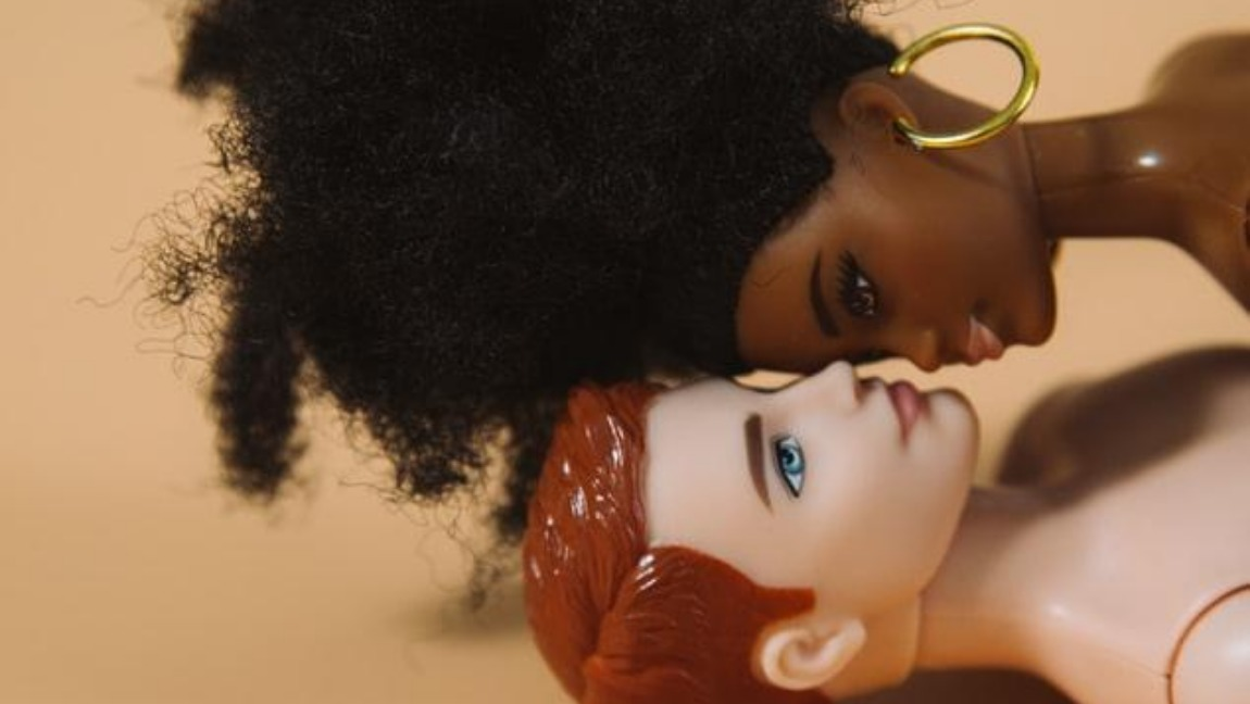 [Image Description: Two dolls lie on top of each other. The one at the bottom has short red hair and the one on top has black curly hair and hoop earrings.] via Unsplash