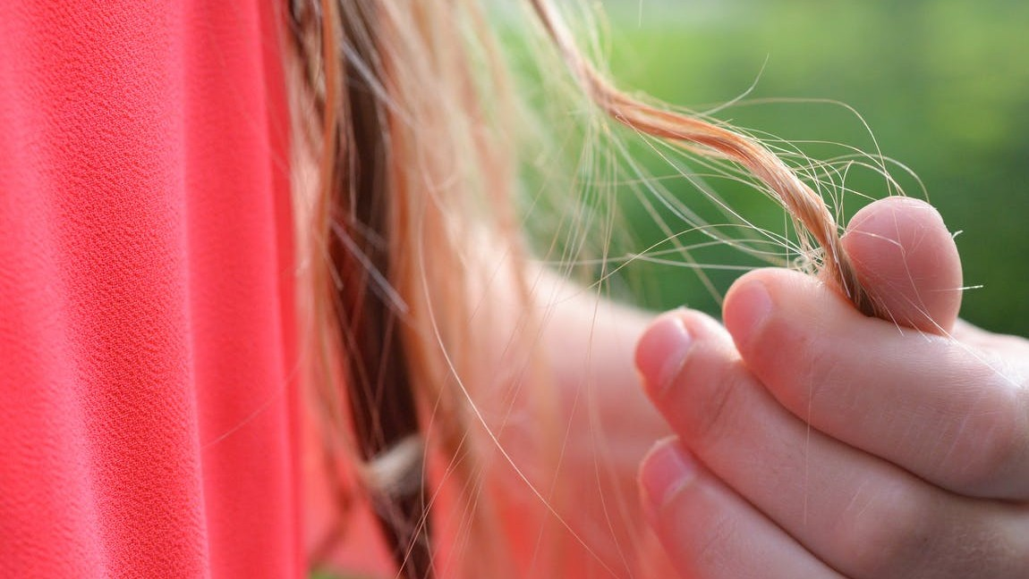 [Image Description: A zoomed in photo of a hand holding onto a few strands of hair.] Via Pexels